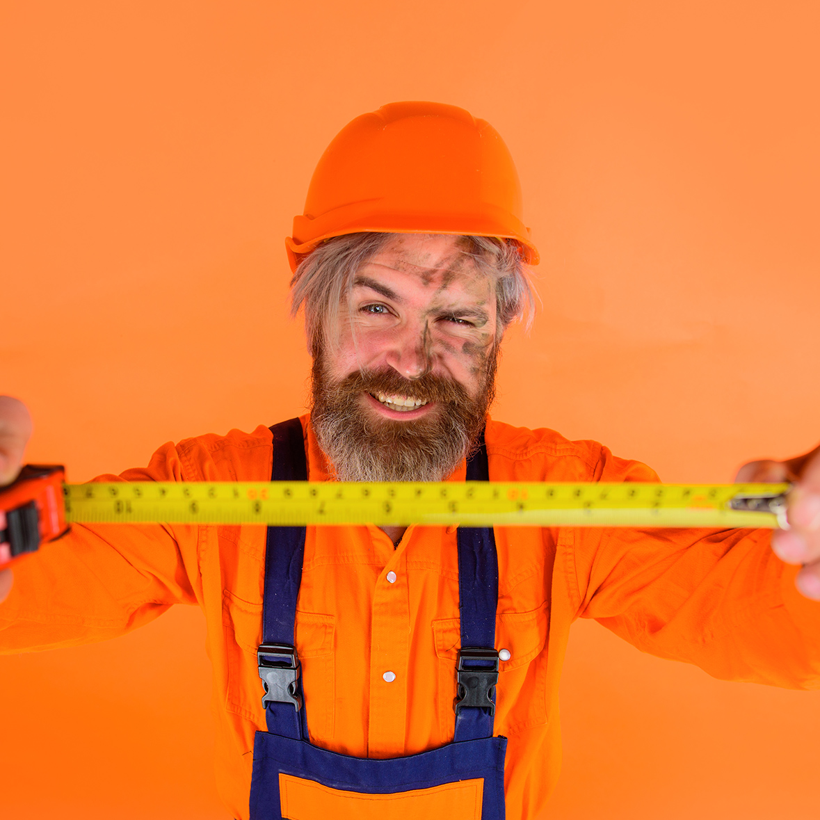 Builder with measure tape. Selective focus. Measuring device. Construction worker. Worker use tape measure. Builder equipment. Bearded builder in protective helmet. Repair tools