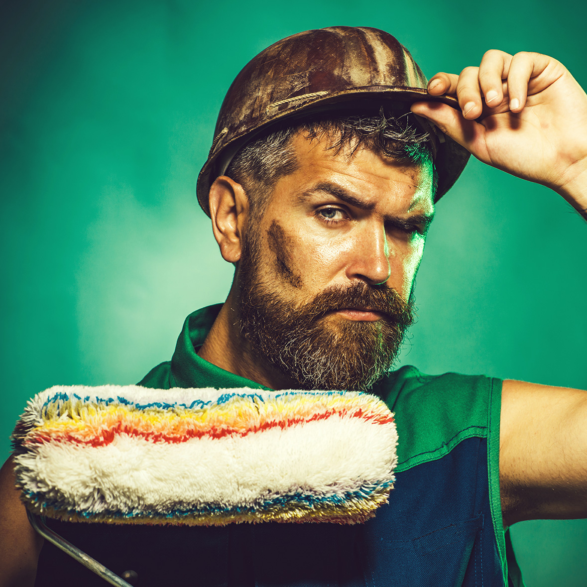 Male painter with paint roller. Professional painter with painting roller in protective helmet. Interior working with paint roller in room. Professional painting. Handsome bearded decorator. Closeup.