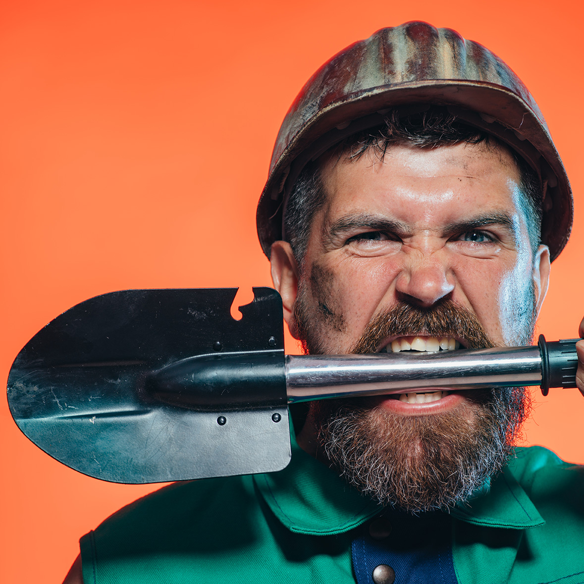 Construction and mining concept. Builder or miner wears helmet and holds shovel in teeth. Man with angry face isolated on orange background. Bearded man wears working uniform and protective helmet.